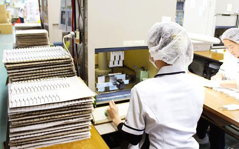 左に積まれた部品をひとつひとつ機械にかけ、手作業でチェックする