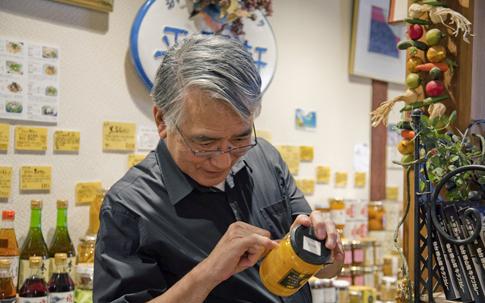 「夏みかんスライス」(420g 1785 円)を手にとり、商品が持 つストーリーを語り始める森田さん。