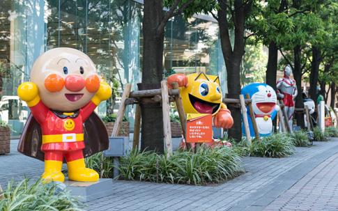 本社ビルの周りには、バンダイとともに歩んできたキャラクターがズラリと並ぶ。 (©やなせたかし/フレーベル館・TMS・NTV ©BNGI ©藤子プロ・小学館・テレビ朝日・シンエイ・ADK ©円谷プロ)