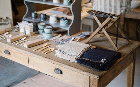 左のカトラリーと器は、鹿児島県の「ONE KILN」のもの。右手前にあるのは、福岡を拠点にオーガニックコットンや手紬の糸を使って、ガラ紡績機で織る「Suno & Morruson」のストールとウーブルオリジナルのコースターなど。