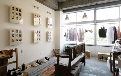 """スニーカーのほかにも大阪のブランド「maillot」の洋服も。取材に訪れた日、普段はスニーカーが飾ってあるという壁を使って、編集者・岡本 仁さんのポラロイド写真展""""MY DAYS BEFORE INSTAGRAM.""""が行われていた。"""