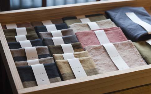 染織家の菜々子さんが染めた草木染めのコースターや手拭いが販売されている。