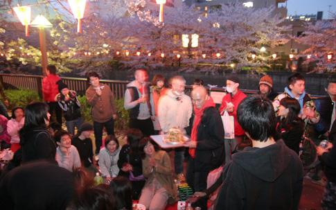 宮村さんが過去に開催したお花見の様子。中央の赤いマフラーが宮村さん。まさに大宴会! 今年の開催を楽しみにしている人も多いそう。